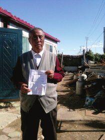 """10月17日,刘春山站在自家门前,向记者展示""""解除劳动教养证明书""""。去年4月18日,他因""""上访扰乱公共秩序""""被送入辽宁营口市劳教所。图/记者谭君"""
