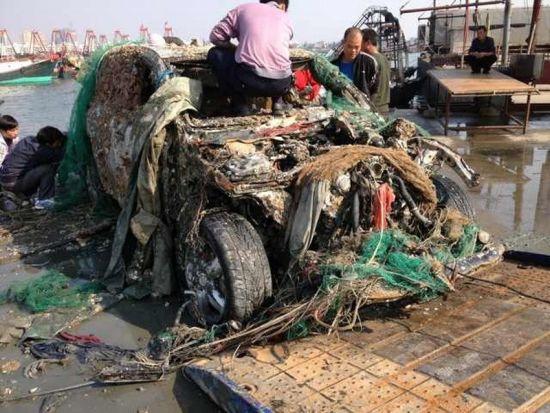"""由于汽车残骸和网袋缠绕在一起难以解脱,小马无奈只好将它拖回了外贸码头,然后请车把它吊上岸。汽车出水后,有人认出这竟是一辆过百万的保时捷""""卡宴""""越野车。图为被打捞出来的保时捷缠满了杂物,渔民爬上车顶试图解开。罗秋鹏/东方IC"""