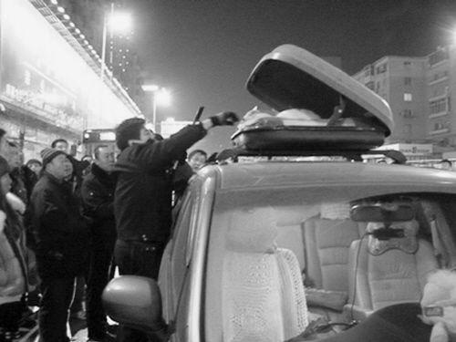 民警在本田车顶棚上的行李箱里搜枪