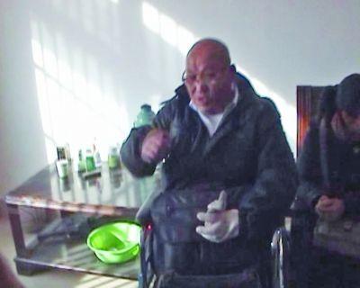 老孟坐在轮椅上和民警交流。