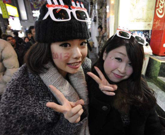 2012年12月31日,日本东京涩谷,人们在迎新年活动中。当日,日本东京涩谷举行倒计时活动,迎接新年的到来。新华社发(关贤一郎 摄)