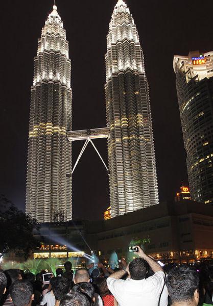 12月31日,人们聚集在马来西亚首都吉隆坡的地标性建筑——马来西亚石油公司双塔下,参加倒计时迎新年活动。新华社记者林昊摄
