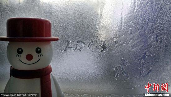 12月31日,沈阳市民李先生利用窗花绘制吉祥图案,喜迎2013年的到来。图片来源:CFP视觉中国