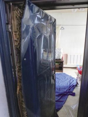 邻居大门被炸变形   ■本报记者 王雨 摄
