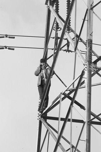 女子站在高压电线塔上,不时打电话。