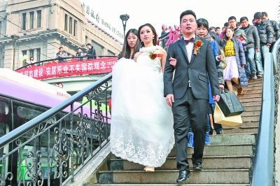 夏敬伟接到新娘谢蝶后,两人手牵手走过江汉路天桥。