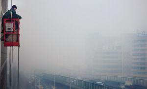 """昨日9时许,皇姑区崇山东路上大雾已将高架桥""""吞没"""",一位工人正在楼外作业 ■本报记者 王野 摄"""