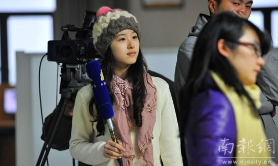 """1月21日,""""奶茶妹妹""""到南京电视台做实习生。图为""""奶茶妹妹""""在采访现场。 南报网记者 朱皓 杜文双摄"""