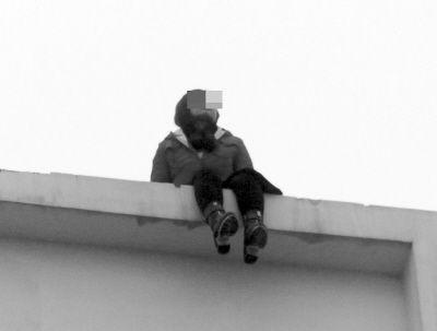 女子(左图画圈处)坐在18楼的楼顶。
