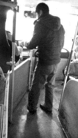 昨日,一名206路公交车司机伸手接过乘客给的1元纸币,收钱后并没有放人投币箱中 ■本报记者 张诗尧 摄