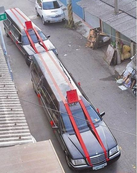 台南柳营的葬仪社业者办婚事,用加长型的殡葬礼车迎娶,引来路人注目。来源:台湾《苹果日报》