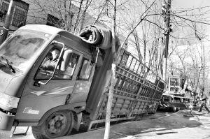 拉啤酒的货车车轮陷进深坑,大吊车正在实施救援 张诗尧 摄