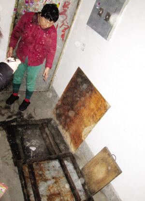 居民胡大娘掀开铁板给记者看下面的大坑