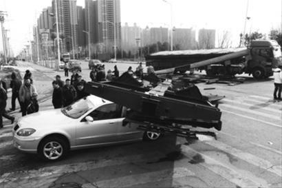 昨日下午,在沈阳市于洪区细河路南阳湖街交汇处,一辆满载着火车车厢底部钢板的卡车在急转弯时,钢板倾倒将一辆私家轿车后排砸毁,车内无人受伤。 记者 姜旭 摄