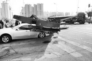 小轿车车顶被砸塌,后车厢严重变形■本报记者 邢子慕 摄