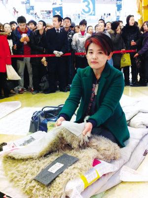 大连一商场内,女子带行李到店门前维权。 本报记者 王宇 摄