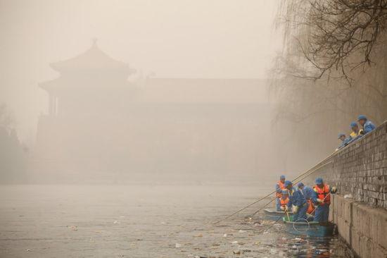 2月28日,故宫外筒子河,环卫工人破冰后打捞河道内的垃圾。