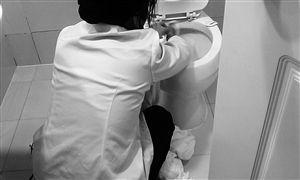 客房服务员用洗脸毛巾擦马桶,脚边还堆着浴巾和另外一块洗脸毛巾