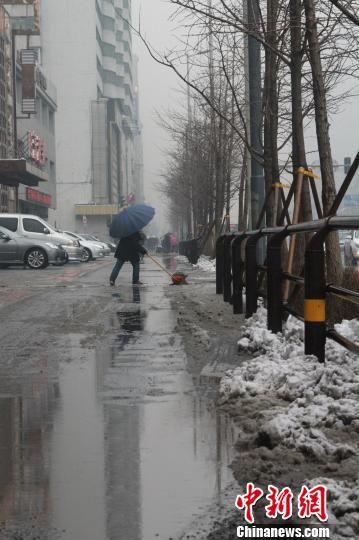"""降雪导致沈阳街道""""泥泞不堪"""",市民清理商铺门前的雪水混合物。"""