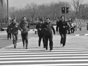 行人在急速奔跑■本报记者 蔡敏强 摄