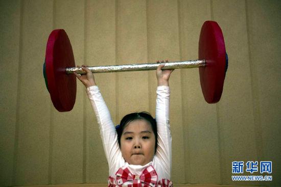 地时间2012年9月13日,朝鲜平壤,女孩子举着玩具杠铃玩耍
