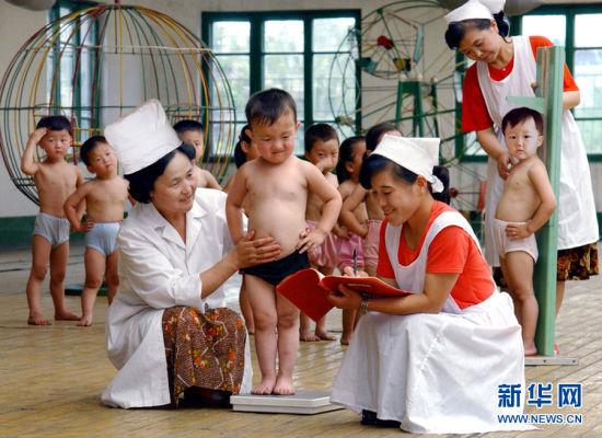 当地时间2008年6月,朝鲜平壤,护士给朝鲜小男孩称体重