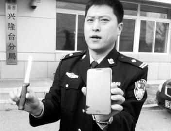 警方展示小强(化名)抢劫时使用的尖刀和抢来的手机。 记者 徐刚 摄