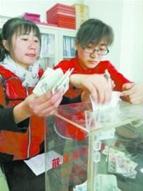 王娜(右)和尤丹丹(左)将募集的善款送至沈阳市红十字会。记者 杨宝顶 摄