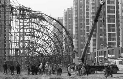 昨日中午,在沈阳市雅居街一处建筑工地,成排的木头架子倒在马路上,夹在架子中间的一排电线杆也都一同倒下。辽沈晚报、北国网记者 查金辉 摄