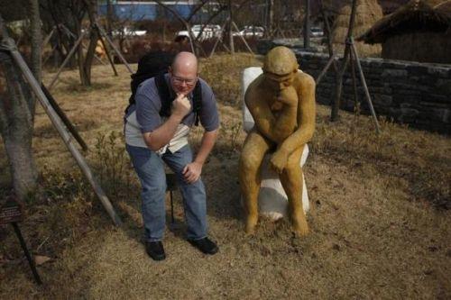 一名游客摆出与雕像相同的