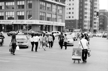 当绿灯亮起行人过马路时,转向车辆总是抢先一步拦住行人的脚步。 本版图片由本报见习记者 李英博摄