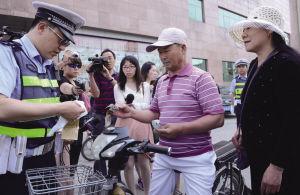 交警对不按规定车道行驶的电动车驾驶人进行处罚 。本报记者 王舜天 摄
