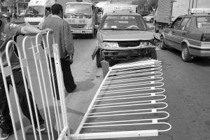 """出租车""""骑""""上马路中间的隔离护栏 。■本报记者 王舜天 摄"""