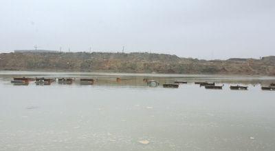"""大坝下方变成了""""堰塞湖"""",""""湖""""中有十几辆被淹没的太脱拉露出""""小脑袋""""。"""