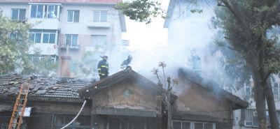 屋顶被烧出窟窿,消防人员紧急灭火