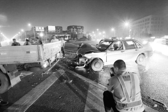 事故现场路面上散落着很多汽车零部件和玻璃碴。摄影记者孙振芳