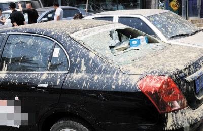几辆车被溅上泥,黑色车后挡风玻璃被砸碎