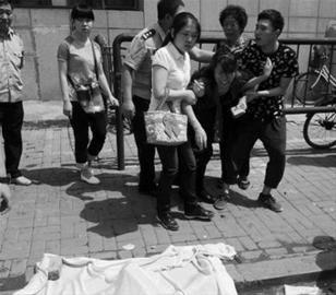 昨日,沈阳市皇姑区华山路附近某高层大厦,一名年轻男子从27楼坠下。家人闻讯赶到现场痛哭不已。 读者供图