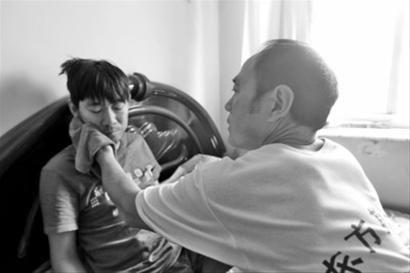 王纯平在给儿子王宁擦脸。