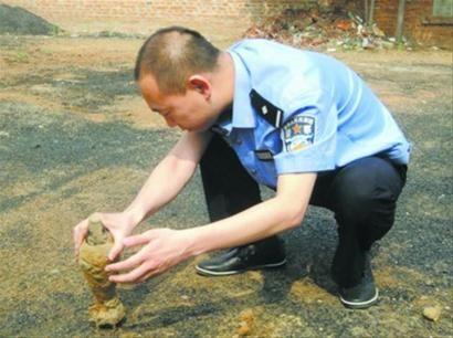 锦州黑山县新兴派出所民警正在鉴定孩童们无意挖出的迫击炮弹。 警方供图