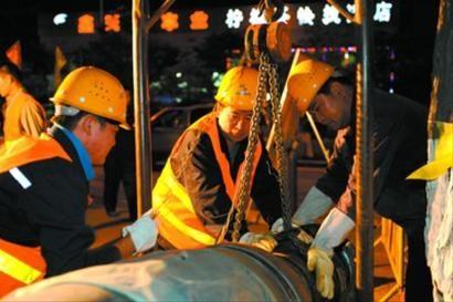 图为工人们正在铺装管道阀门