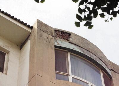 楼顶一处墙皮已经脱落,露出了红砖。