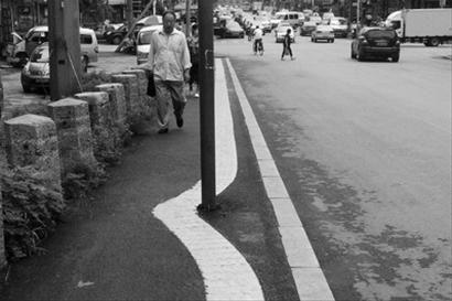 昨日下午,在抚顺市十一道街,该处盲人道的中部绕开铁柱,致使弯出一个约150°的钝角。北国网、辽沈晚报记者 白琳 摄