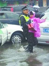 大雨中执勤的校警抱着上学的孩子趟水过马路。