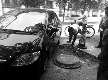 昨日上午,在沈阳市和平区辽源路上,发生事故的车辆还停在下水井坑旁边,车辆的两个前轮已经损坏。 北国网、辽沈晚报记者 胡婷婷 摄