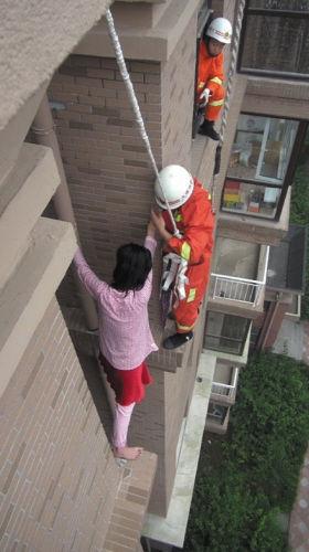 消防人员身系安全绳,将女子安全拽回室内