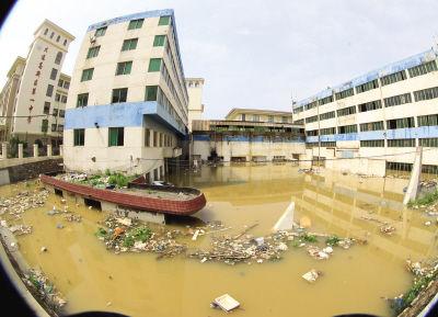 两幢楼泡在黄色的污水中,千余平方米的院子里已成一片汪洋。
