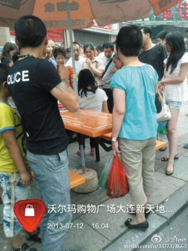 女子(中间白色衣服披肩发)被热心人围着劝说。