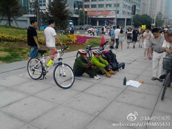 俩打扮成驴友的人在市府广场乞讨回贵州的路费,旁边还摆着专业自行车。微博截图