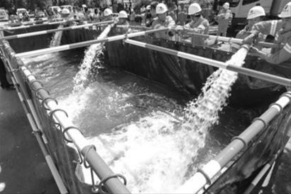 昨日下午,沈阳水务集团排水管理处在万柳塘公园举行了防汛应急演练,工作人员往防汛储水槽内排水。北国网、辽沈晚报记者 查金辉 摄